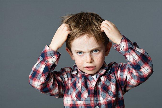 Chłopiec drapiący się po głowie przez wszawicę